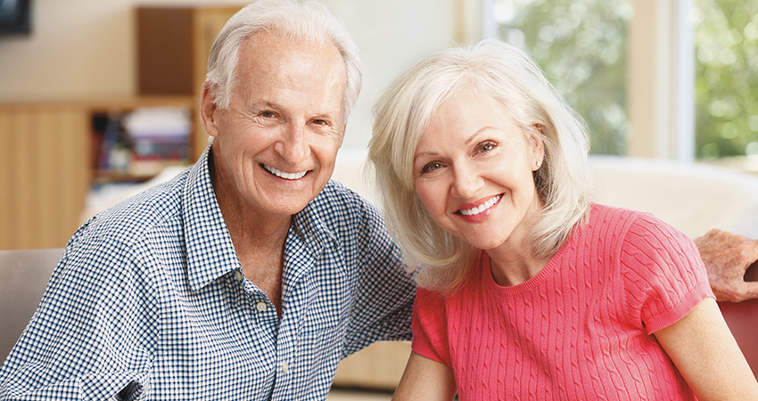 Retired couple smiles with new dental implants while sitting together on couch